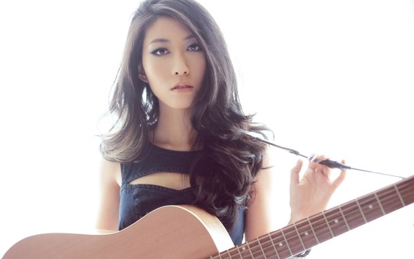 Qu Wanting holding a guitar.
