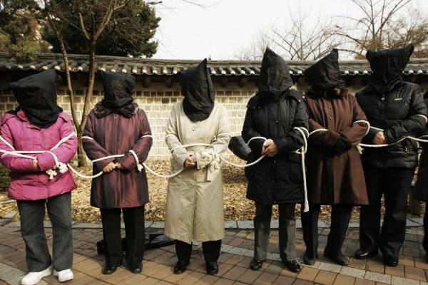 2008 December 9, Seoul, South Korea, North Korean refugees pose to be North Korean fugitives, protesting the North Korean government. REUTERS/Lee Jae-Won