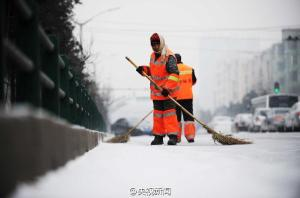 A sanitation worker sweeps a snow covered street