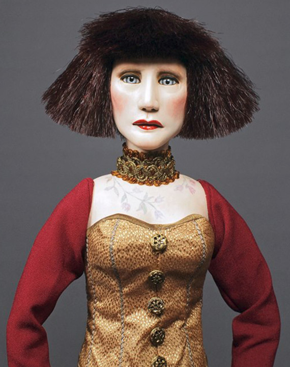 """YEAR: 2013 SIZE: 19""""h x 5"""" diameter base MEDIUM: Mixed medium, resin clay, cloth, beaded trim. tattoo art. Kanekalon synthetic hair, German glass eyes. Posable wood and wire armature. The Figure is mounted on a metal pedestal. EDITION: One-of-a-kind"""