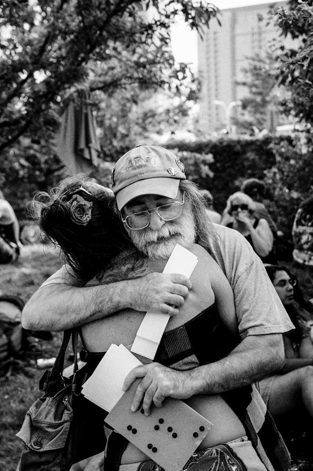 "CHICAGO, ILLINOIS - JULY 4, 2015 - Friends embrace each other while on Shakedown Street before the Grateful Dead's 4th of July ""Fare Thee Well"""