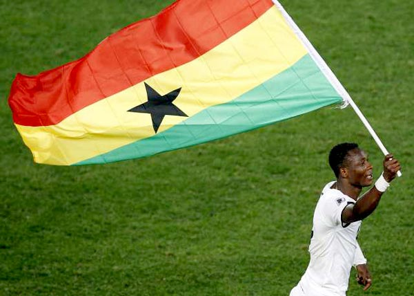 A member of Ghana's Black Stars, the national football team, running with the Ghana flag