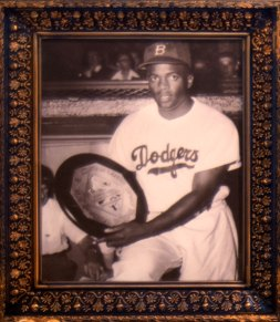 Robinson in a Dodgers uniform posing with an award circa 1948. The City Reliquary Museum