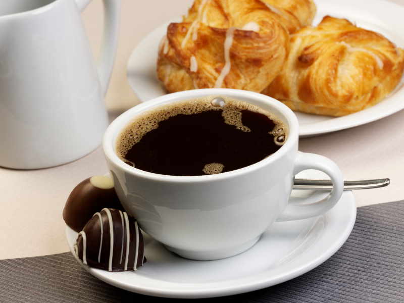 Black coffee in a white cup qith some chocolates.
