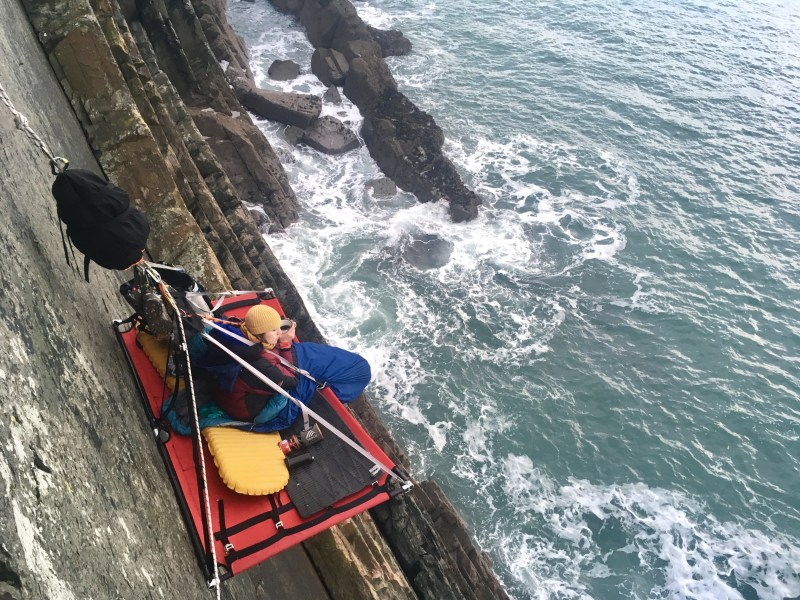 Relaxing on the Portaledge with a coffee, Cliff Camping in Pembrokeshire..