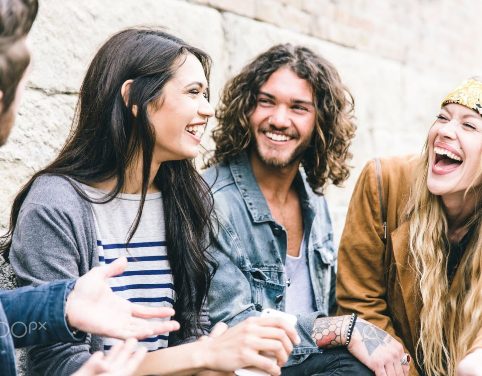 Group of four friends laughing out loud outdoor, sharing good and positive mood