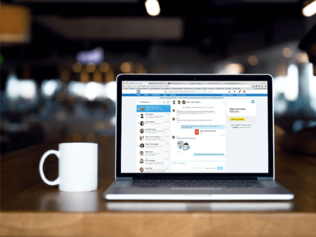 A mug, laptop and LinkedIn's homepage
