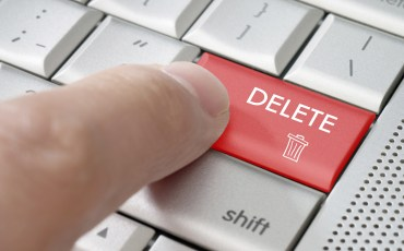 Business concept male finger pointing delete key