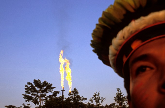 Chief Robinson, the leader of the Cofan Indians and a strong activist in the suit against Texaco. Photographed in front of the Guanta oilrig, Chief Robinson argues that the oil production has contaminated the river nearby as well as members of his community, who live down stream and several other parts of the region. He feels that Ç the government tries to convince us that oil is the future of Ecuador. The oil has only brought catastrophe here. We, the Cofan, are unanimous and determined to protect what is left of the forest. All of Mankind needs it. È