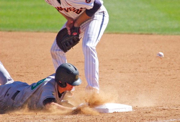 The ball gets by as Ryan Rosa dives back to first. (Photo: Shotgun Spratling)