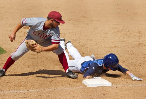Kyle Holder dives back to first base before Tommy Cheek's tag.