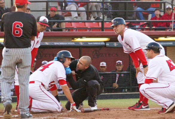 Evan Potter is checked after getting hit by a pitch in the face. (Photo: Shotgun Spratling)
