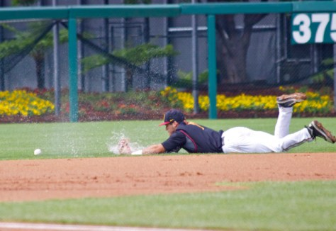 Frankie Rios dives through a puddle trying to get to a ball.