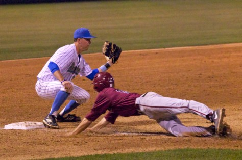 An LMU runner dives back as Chris Keck catches the throw.