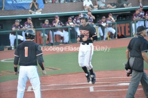 OSU's Andy Peterson hops toward Tyler Smith after both Beavers scored on Danny Hayes' double in the seventh inning