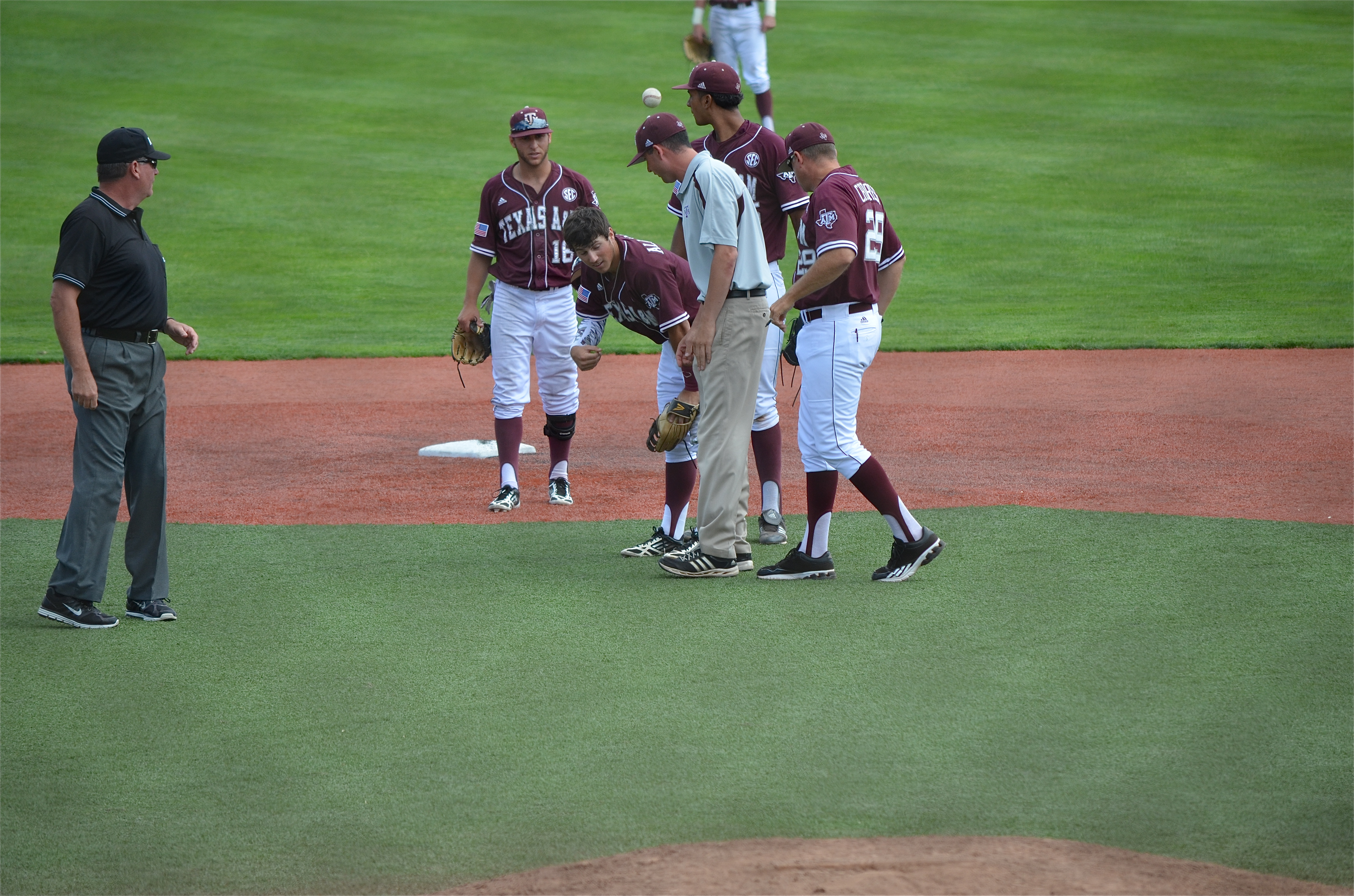 A Texas A&M trainer and coach Rob Childress check on second baseman Blake Allemand. (photo by Aaron Yost)