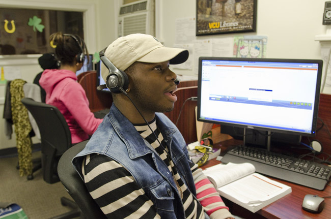 Brian Armstrong, a criminal justice junior at VCU, speaks with an alum at the Goldline call center. The 56 students who work at the center have made nearly 300,000 calls since Goldline started in September 2012. Photo by Chris Conway