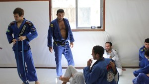 A BJJ black belt gives some students advice at a seminar at the Nova Uniao gym