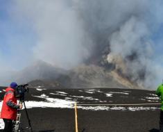 """Figura 3 – 15 Novembre 2011: il Nuovo Cratere di Sud-Est erutta fragorosamente, producendo l'ennesima """"fontana di lava"""". Il nuovo cratere sommitale si accresce sul fianco orientale di quello """"vecchio"""", che rimane inattivo, visibile nella fotografia a sinistra. Foto di Marco Neri."""