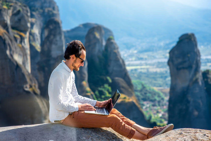 40137640 - well-dressed man working with laptop sitting on the rocky mountain on beautiful scenic clif background near meteora monasteries in greece.