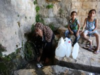 A Palestinian woman fills a jerrican with spring water on June 27, 2016 in Salfit, north of Ramallah, where some of the West Bank village's inhabitants have been without water for days. Tens of thousands of Palestinians in the Israeli-occupied West Bank have gone without water in recent weeks, victims of the latest dispute between Israeli and Palestinian officials over the region's most valuable resource. Photo by Nedal Eshtayah
