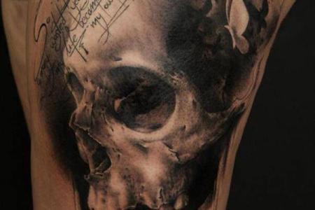 100 skull thigh tattoo