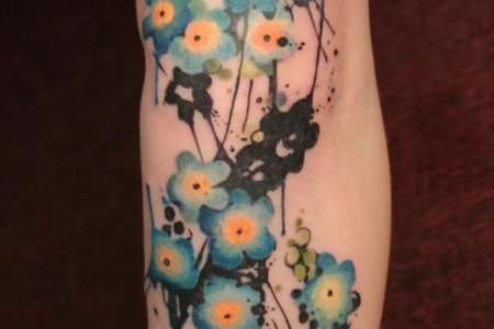 16 tiny blue flowers arm tattoo
