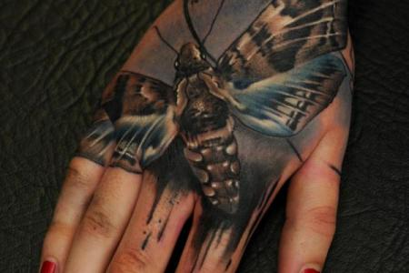 19 moths tattoo on hand for women