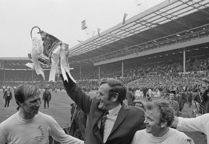 Leeds United F.C. manager Don Revie (1927 - 1989) lifts the 'FA Cup' trophy after his players beat Arsenal F.C. to win the FA Cup Final, Wembley Stadium, London, 6th May 1972. Also shown are Jack Charlton (left), Billy Bremner (1942 - 1997), and Paul Reaney (far right). (Photo by Express/Hulton Archive/Getty Images)
