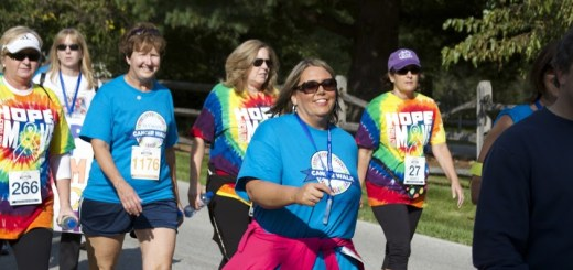 Teams of cancer survivors and their groups of supporters walk.