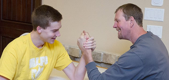 Derrik Smits and his father, Rik, arm wrestle at their house in Zionsville. (Photo by Cindy Goyer)
