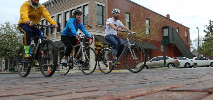 From left, Loren Long, Mallory Wilson and David Wefler ride their bikes along Main Street. (Photo by Ann Marie Shambaugh)