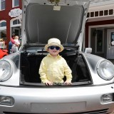 A youngster plays in the trunk of a silver Porsche. (Photo by Theresa Skutt)