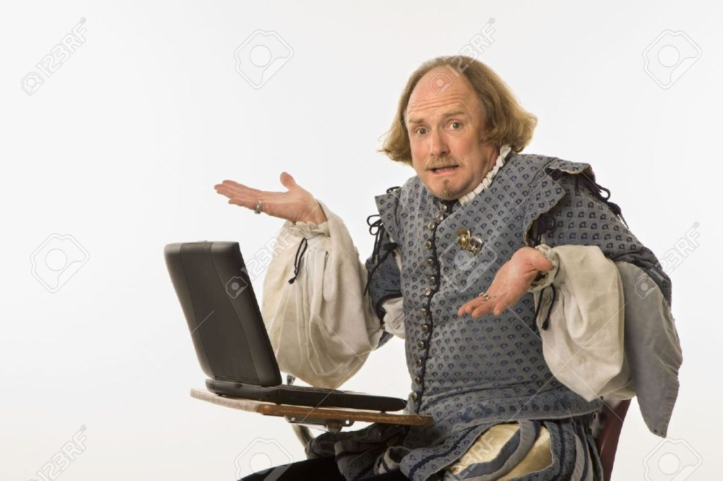2145480-William-Shakespeare-in-period-clothing-sitting-in-school-desk-with-laptop-computer-shrugging-at-view-Stock-Photo