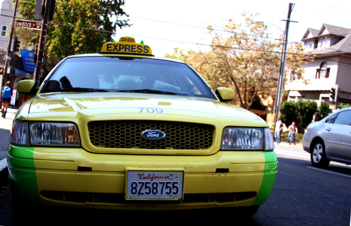 A taxi cab stops in front of Hotel Durant.