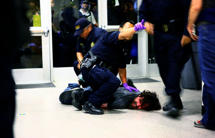 A police officer apprehends a demonstrator in Tolman Hall, where the Day of Action protesters occupied a room. The protest was propelled by persisting state budget cuts to the UC and accompanying tuition increases.