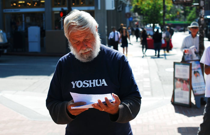 Yoshua, a common sight on the UC Berkeley campus, holds his flyers as he stands near Sproul Plaza.