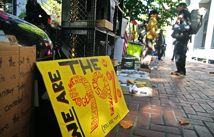 Occupy San Francisco protesters stand near signs and supplies outside the San Francisco Federal Reserve, on Market Street.
