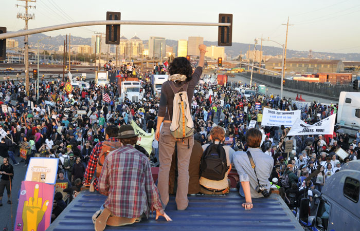 A protester stands with her hand raised atop a semi trailer as protesters march towards the Oakland port from downtown during the Nov. 2 general strike.