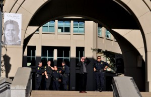 Dan Mogulof and police officers stand at the entrance to the Haas School of Business.