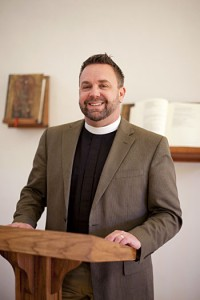 Pastor Jeff Johnson stands at the pulpit in the University Lutheran Church.