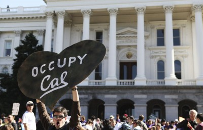 A man holds an Occupy Cal sign in front of the capitol building in Sacramento.