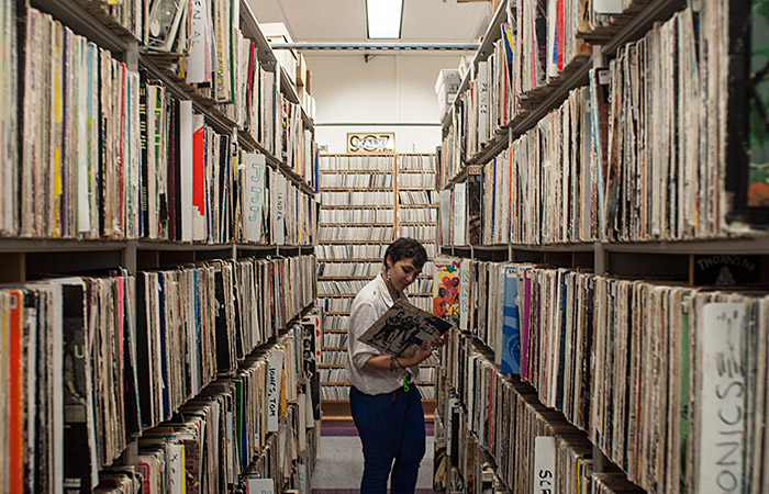 Lena Ghazarian, Operations Coordinator for KALX, searches their library for a record. Over 95,000 titles are housed in their collection.