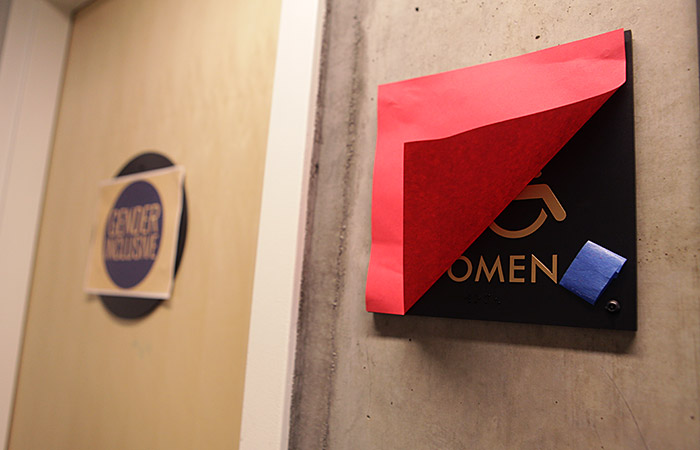 A women's bathroom sign is covered at Martinez Commons. There has been controversy over the usage of differentiated bathrooms as well as shared facilities by residents.