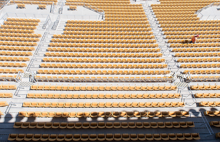 A construction worker walks between the rows of seats in Memorial Stadium during its retrofit. A recently-released report shows that the number of premium seat sales, part of the funding model for the renovation, is lagging behind predictions.