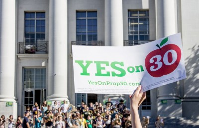 A sign in favor of Proposition 30 is held high during a rally at Sproul Plaza on November 5th.