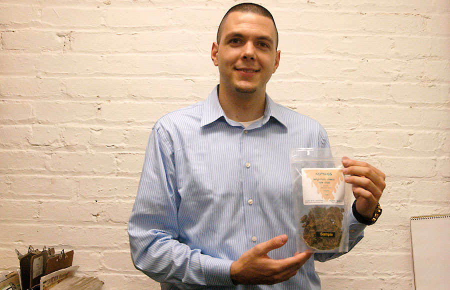"""Yanick Aymon, an International student from Switzerland holds the product Natchos"""" a cheese flavored kale chip which he is marketing for a class."""