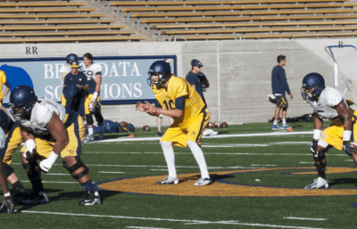 Jared Goff takes a snap at quarterback with Brendan Bigelow in the backfield during Friday's practice