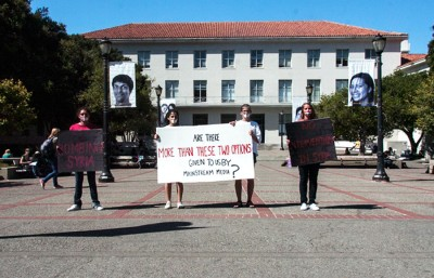 A group of UC Berkeley students stood outside Dwinelle Hall on Monday afternoon holding posters questioning the media's presentation of the recent decision to bomb Syria. The demonstration was intended to garner support for the main protest planned for Tuesday at noon.