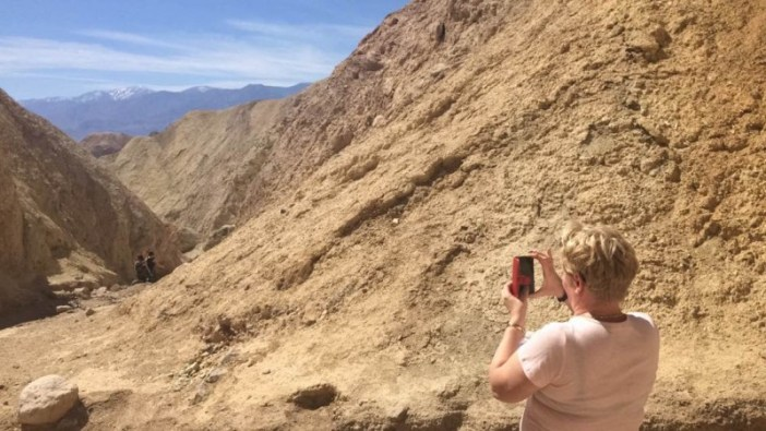 My mom trying her darnedest to take a picture at Death Valley. iPhone's are hard!